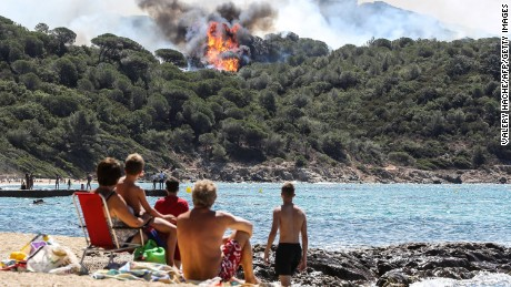 TOPSHOT - People enjoy the beach as they look at a forest fire in La Croix-Valmer, near Saint-Tropez, on July 25, 2017. Firefighters battle blazes that have consumed swathes of land in southeastern France for a second day, with one inferno out of control near the chic resort of Saint-Tropez, emergency services say. / AFP PHOTO / Valery HACHE        (Photo credit should read VALERY HACHE/AFP/Getty Images)