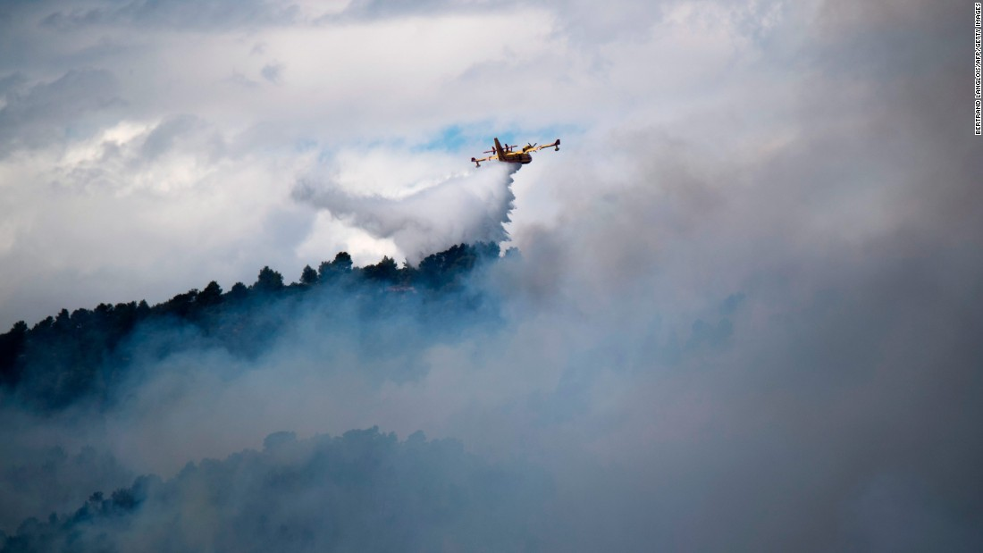 An airplane drops water over a fire in Mirabeau, France, on July 24.