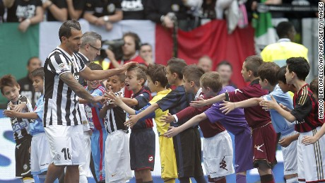 "Juventus' Argentinian forward Carlos Tevez is welcomed by children wearing jerseys of the teams of the Italian championship before to receive the trophy of the Italian Serie A after their last football game of the season Juventus vs Cagliari on May 18, 2014 at the Juventus Stadium in Turin. Juventus won their third consecutive ""scudetto"". AFP PHOTO / MARCO BERTORELLO        (Photo credit should read MARCO BERTORELLO/AFP/Getty Images)"