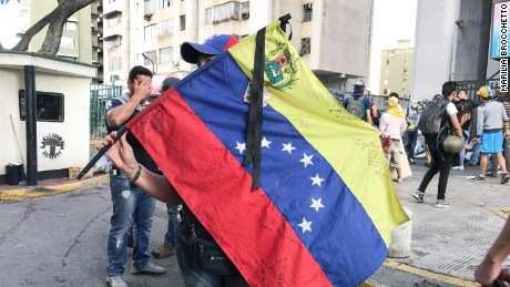 A protester waves the national flag in Caracas on Wednesday.