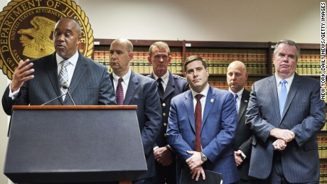 US Attorney Robert Capers, left, flanked by members of the FBI and Nassau and Suffolk County Police, speaks at a news conference in March. They announced the indictment of suspects in seven gang-related slayings.