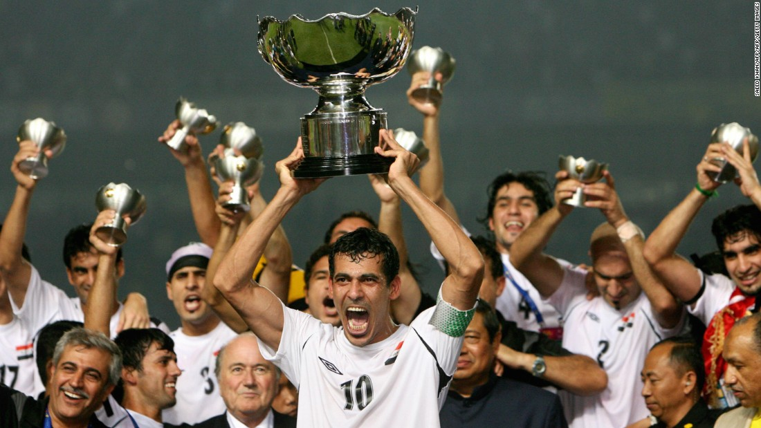 Iraq's captain and goalscorer in the final, Younis Mohmoud, holds the Asian Cup trophy aloft.