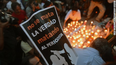 "Colleagues, relatives and friends of murdered journalists place candles and pictures in an altar erected at the Independence Angel monument in Mexico City on May 5, 2012 during a vigil to protest against violence towards the press. On Thursday Mexican security forces found the dismembered bodies of missing news photographers Guillermo Luna Varela and Gabriel Huge and two other people in bags dumped in a canal in the eastern state of Veracruz. The bodies of the photographers, who worked for the Veracruz news photo agency, also showed signs of torture. The postre reads ""The Truth is Not Killed by Killing The Journalist"".   AFP PHOTO/Yuri CORTEZ        (Photo credit should read YURI CORTEZ/AFP/GettyImages)"