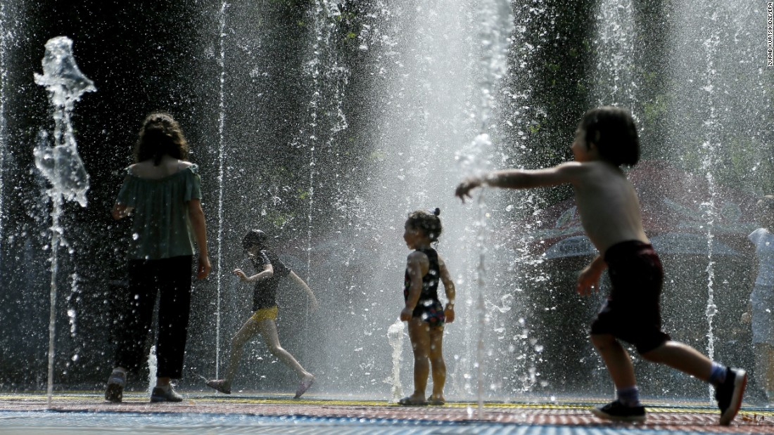 Children run through a fountain to cool off in Tbilisi, Georgia, on Wednesday, July 26.