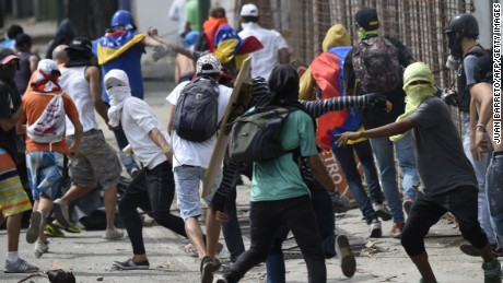 Anti-government activists clash with troops in Caracas on Thursday, the second day of a general strike.