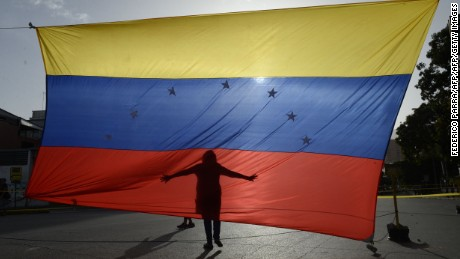 TOPSHOT - A person's shadow is cast on a Venezuelan national flag in Caracas on July 10, 2017. Venezuela hit its 100th day of anti-government protests Sunday, amid uncertainty over whether the release from prison a day earlier of prominent political prisoner Leopoldo Lopez might open the way to negotiations to defuse the profound crisis gripping the country. / AFP PHOTO / FEDERICO PARRA        (Photo credit should read FEDERICO PARRA/AFP/Getty Images)