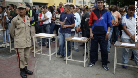 "Venezuelans line up to cast their ballot at a polling station in Caracas on July 30, 2017. Polls opened in Venezuela on Sunday for the election of a new, all-powerful ""Constituent Assembly"" that President Nicolas Maduro promised would end his country's political and economic crisis by rewriting the constitution. The vote has been fiercely opposed by months of deadly street protests and criticized internationally. Venezuela's opposition says it is a bid for the beleaguered Maduro to cling to power by getting around the parliament controlled by its lawmakers."