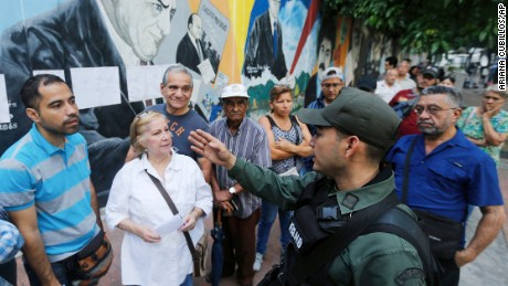 A Bolivarian National Guard officer instructs voters Sunday outside a polling station in Caracas.