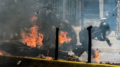Police officers react after a devise exploded as they rode past during a protest against the elections for a Constituent Assembly in Caracas on July 30, 2017.