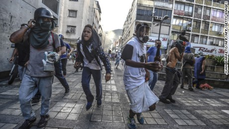 Anti-government activists scatter upon being charged by riot police during a protest against the election of a Constituent Assembly proposed by Venezuelan President Nicolas Maduro, in Caracas on July 30, 2017. Deadly violence erupted around the controversial vote, with a candidate to the all-powerful body being elected shot dead and troops firing weapons to clear protesters in Caracas and elsewhere. / AFP PHOTO / JUAN BARRETO        (Photo credit should read JUAN BARRETO/AFP/Getty Images)