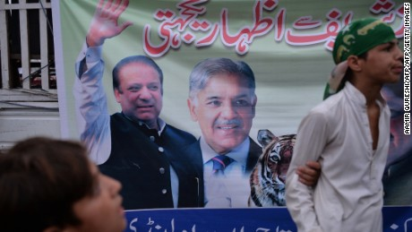 Supporters of ousted Pakistani prime minister Nawaz Sharif stand next to a banner featuring images of Sharif (L) and his brother Shahbaz Sharif (C) on July 29.