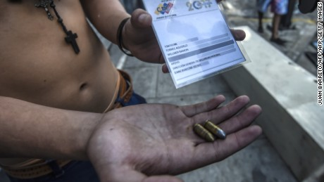 An anti-government activist shows an ID card and 9mm two 9mm bullets seized to a presumed security forces' infiltrator during a protest against the election of a Constituent Assembly proposed by Venezuelan President Nicolas Maduro, in Caracas on July 30, 2017. Deadly violence erupted around the controversial vote, with a candidate to the all-powerful body being elected shot dead and troops firing weapons to clear protesters in Caracas and elsewhere. / AFP PHOTO / JUAN BARRETO        (Photo credit should read JUAN BARRETO/AFP/Getty Images)