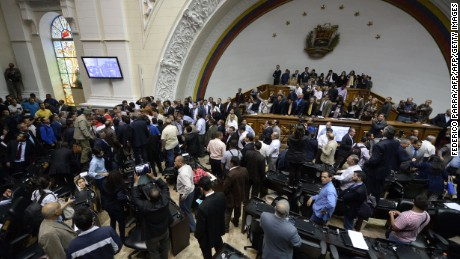 "Supporters of Venezuelan President Nicolas Maduro force their way to the National Assembly during an extraordinary session called by opposition leaders, in Caracas on October 23, 2016.  The opposition Democratic Unity Movement (MUD) called a Parliamentary session to debate putting President Nicolas Maduro on trial to ""restore democracy"" in an emergency session that descended into chaos as supporters of the leftist leader briefly seized the chamber. / AFP / FEDERICO PARRA        (Photo credit should read FEDERICO PARRA/AFP/Getty Images)"