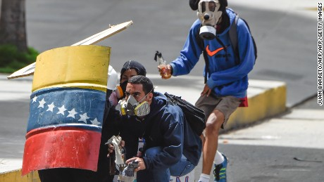 TOPSHOT - Venezuelan opposition activists remain behind a shield as they clash with riot police during a protest against Venezuelan President Nicolas Maduro in Caracas on July 10, 2017.  Venezuela hit its 100th day of anti-government protests Sunday, amid uncertainty over whether the release from prison a day earlier of prominent political prisoner Leopoldo Lopez might open the way to negotiations to defuse the profound crisis gripping the country. / AFP PHOTO / JUAN BARRETO        (Photo credit should read JUAN BARRETO/AFP/Getty Images)