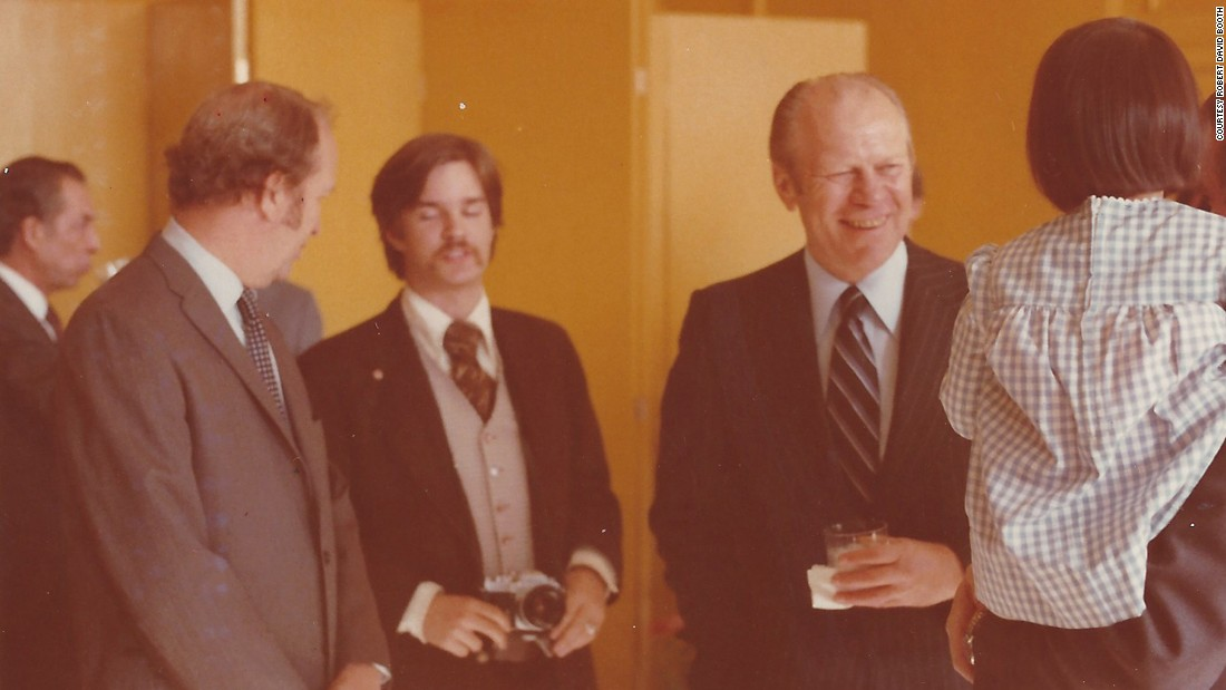 "President Gerald Ford, right, visited the US Beijing Liaison Office in 1976. Booth, seen here holding a camera, was responsible for assisting the Secret Service with Ford's security on the ground. ""My role was guaranteeing that no one came into his immediate area uninvited,"" Booth remarked. Booth's lapel pin acted as a secret signal to his fellow Secret Service special agents and White House staff that he was armed. ""I probably have my Smith and Wesson  Model 19 .357 magnum attached to my belt,"" he explained."