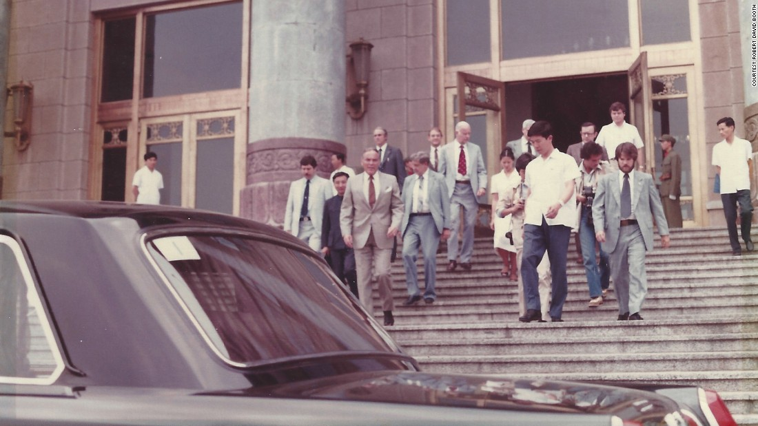 On the right, wearing a suit and tie, Booth helps escort US Secretary of State Alexander Haig, in the foreground on the left, to a waiting security motorcade positioned at the bottom of the staircase at the Great Hall of the People in Beijing, China.