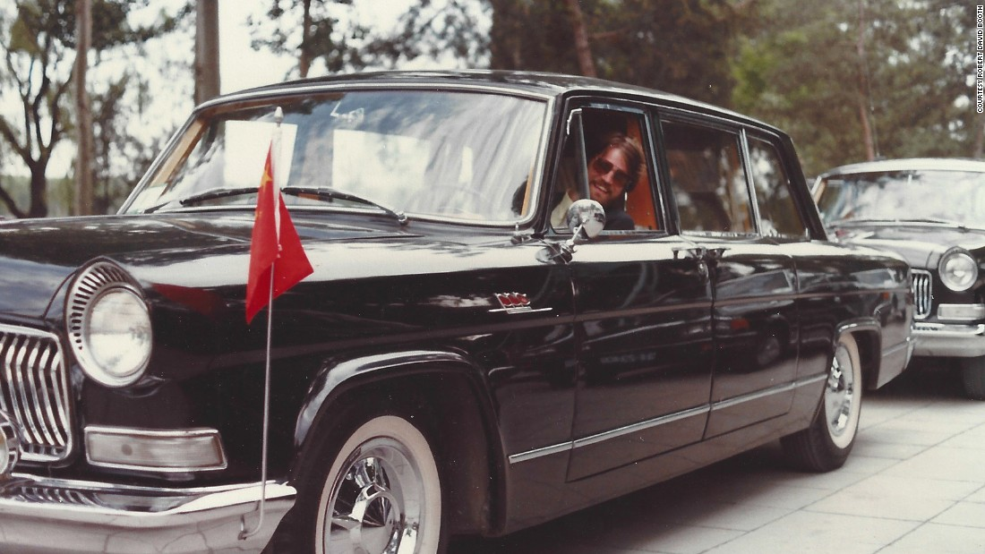 Booth poses behind the wheel of a Chinese diplomatic car in Beijing in 1981.