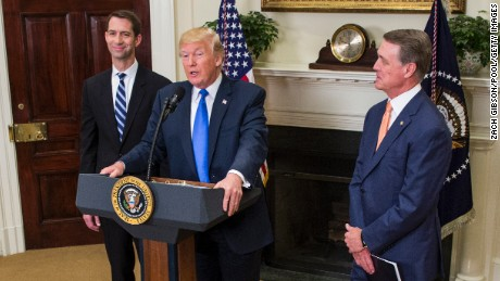 President Donald Trump makes an announcement with Sen. Tom Cotton, at left, an Arkansas Republican, and Sen. David Perdue, at right, a Georgia Republican, in the Roosevelt Room at the White House in August 2017. (Photo by Zach Gibson - Pool/Getty Images)