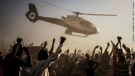 Supporters of Kenyan presidential candidate Raila Odinga wave as he departs in a helicopter after addressing a rally held by his coalition party The National Super Alliance (NASA) in Kisumu on August 3, 2017. 