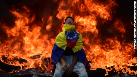 TOPSHOT - A Venezuelan opposition activist is backdropped by a burning barricade during a demonstration against President Nicolas Maduro in Caracas, on April 24, 2017. Protesters rallied on Monday vowing to block Venezuela's main roads to raise pressure on Maduro after three weeks of deadly unrest that have left 21 people dead. Riot police fired rubber bullets and tear gas to break up one of the first rallies in eastern Caracas early Monday while other groups were gathering elsewhere, the opposition said.  / AFP PHOTO / Ronaldo SCHEMIDT        (Photo credit should read RONALDO SCHEMIDT/AFP/Getty Images)