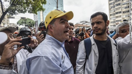 The president of the National Assembly, Julio Borges (L) participates in a protest of doctors and other health care personnel in Caracas on May 22, 2017.  Doctors rallied in Venezuela on Monday in the latest street protests against the government of President Nicolas Maduro, as a young man lay in hospital after being set on fire by an angry crowd. / AFP PHOTO / JUAN BARRETO        (Photo credit should read JUAN BARRETO/AFP/Getty Images)