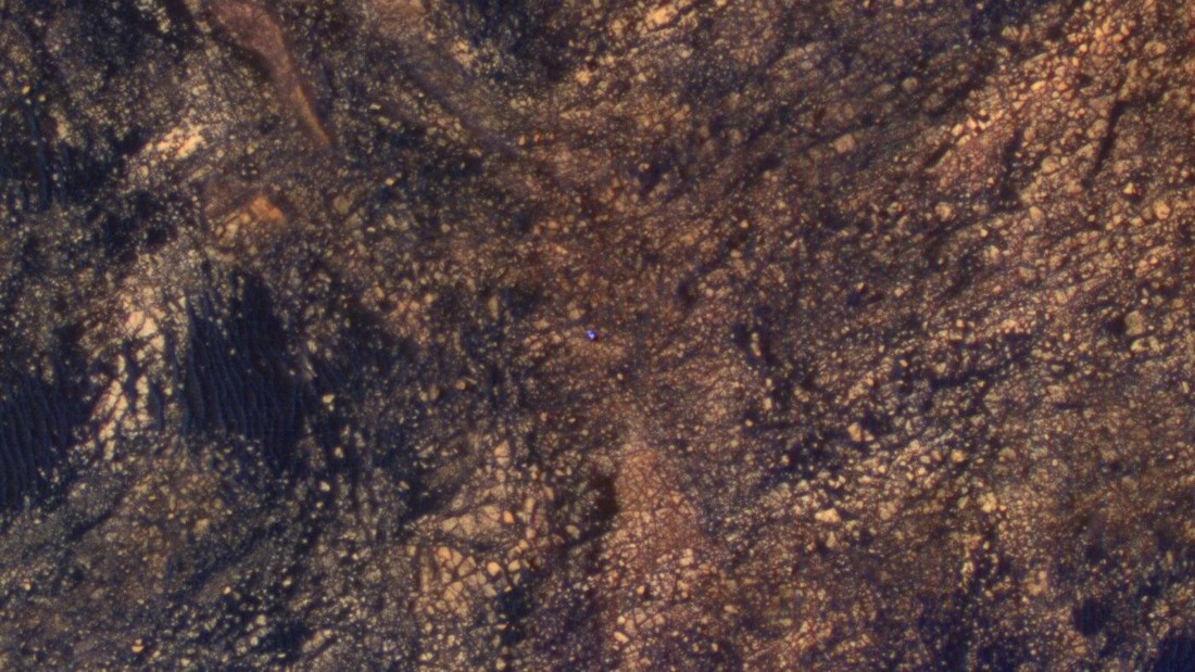The bright blue speck in the middle of this image is NASA's Curiosity Mars rover. The image was taken from another NASA spacecraft, Mars Reconnaissance Orbiter, which is in orbit above the planet, on June 6, 2017.