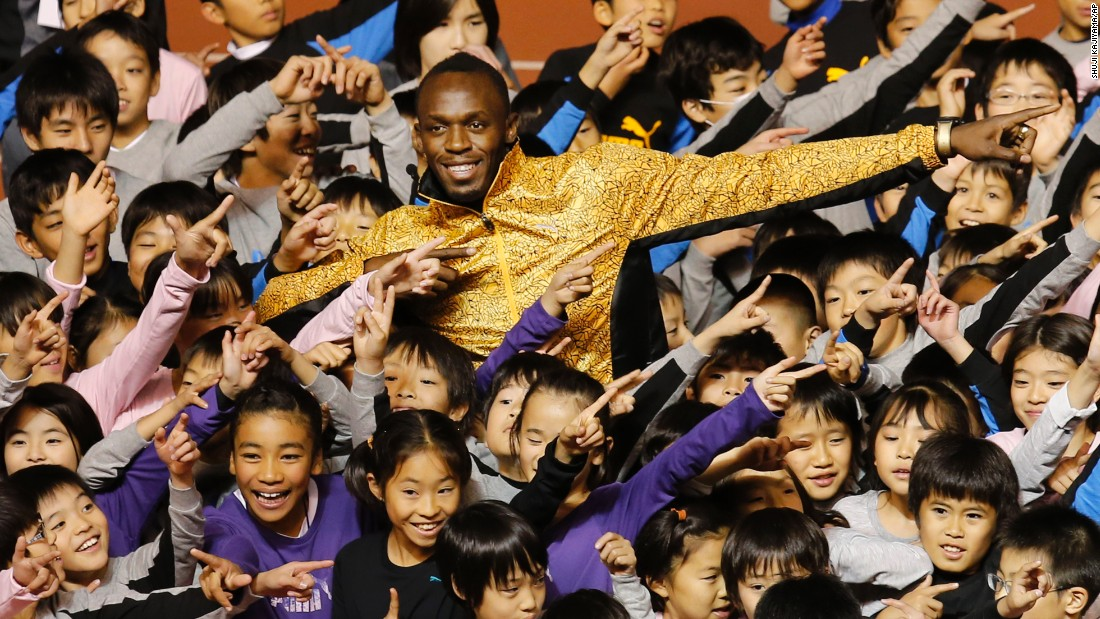 Bolt and children do his signature pose during a track clinic in Tokyo in 2013.