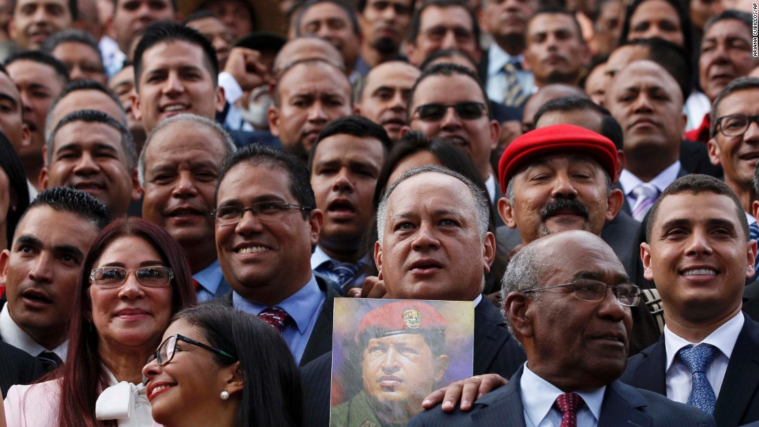Diosdado Cabello, a member of Venezuela's National Constituent Assembly, holds an image of Venezuela's late President Hugo Chavez as delegates gather for a group photo following their swearing-in ceremony on Friday, August 4.