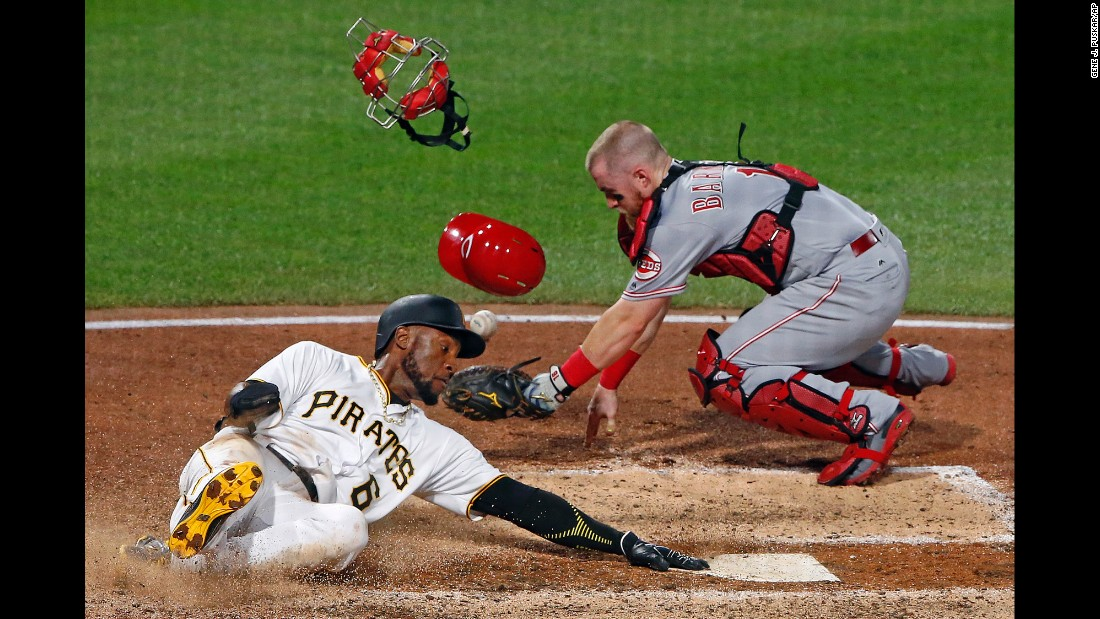 Cincinnati catcher Tucker Barnhart drops the ball as Pittsburgh's Starling Marte slides into home on Wednesday, August 2.