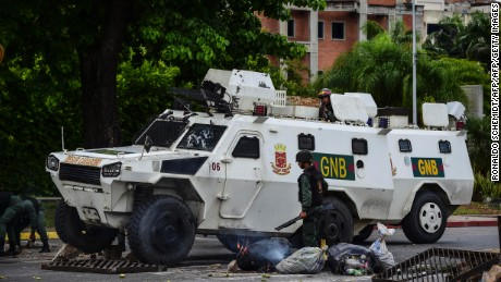 "A National Guard vehicle goes through a barricade built by anti-government activists in Venezuela's third city, Valencia, on August 6, 2017, a day after a new assembly with supreme powers and loyal to President Nicolas Maduro started functioning in the country. In the video posted online earlier, allegedly at an army base used by the National Bolivarian Armed Forces in Valencia, a man presenting himself as an army captain declared a ""legitimate rebellion... to reject the murderous tyranny of Nicolas Maduro"" and demanded a transitional government and ""free elections."" After the video surfaced, military chiefs said troops had put down the ""terrorist"" attack.   / AFP PHOTO / Ronaldo SCHEMIDT        (Photo credit should read RONALDO SCHEMIDT/AFP/Getty Images)"
