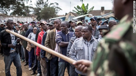 A police officer directs voters toward the back of the line at a Nairobi polling station.