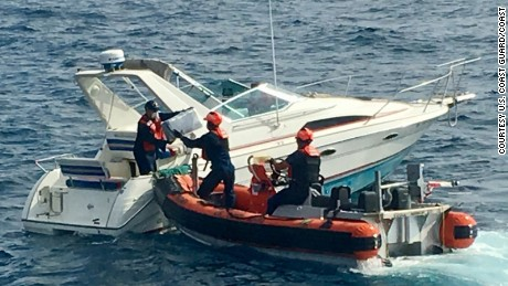 Crew members of Coast Guard Cutter Sea Otter transfer the packages off the suspects' boat.