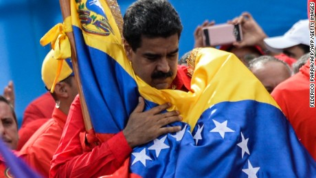 "TOPSHOT - Venezuelan President Nicolas Maduro holds a national flag during the closing of the campaign to elect a Constituent Assembly that would rewrite the constitution, in Caracas on July 27, 2017 on the second day of a 48-hour general strike called by the opposition. Venezuela's opposition called for a nationwide protest on Friday in outright defiance of a new government ban on demonstrations ahead of a controversial weekend election. ""The regime declared we can't demonstrate... We will respond with the TAKING OF VENEZUELA tomorrow,"" the opposition coalition, the Democratic Unity Roundtable, said Thursday on its Twitter account.  / AFP PHOTO / Federico PARRA        (Photo credit should read FEDERICO PARRA/AFP/Getty Images)"