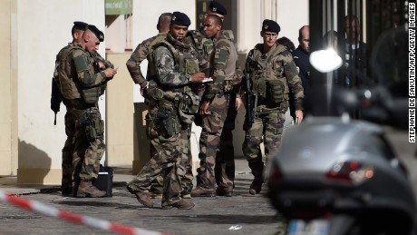 French soldiers gather at the site where a car slammed into soldiers on patrol in Levallois-Perret, outside Paris, on August 9, 2017.