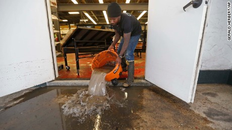 Dwayne Boudreaux Jr., the owner of Circle Food Store, dumps out dirty water Monday that was vacuumed up from the store after weekend flooding in New Orleans.