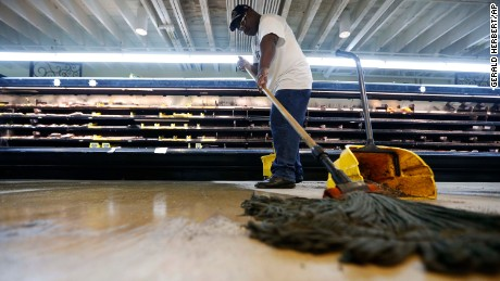 Randy Davis, manager at the Circle Food Store, mops the floor Monday after the store flooded in weekend storms in New Orleans.