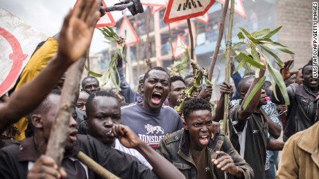 Supporters of opposition presidential candidate Raila Odinga shout and brandish sticks during a protest in the Mathare slums of Nairobi on Wednesday.
