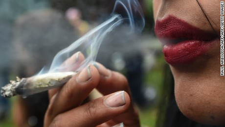 "An activist smokes a joint during a prostest under the motto ""No vamos a pagar, lo vamos a pegar"" (something like 'We are not going to pay for it, we are going to get the kick out of it"") against the imposing of fines for smoking marijuana by police according to their new code, in Bogota, on August 1, 2017 / AFP PHOTO / Raul Arboleda        (Photo credit should read RAUL ARBOLEDA/AFP/Getty Images)"