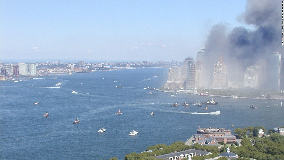 The view north from above Governor's Island shows a fleet of diverse vessels approaching smoke-filled Lower Manhattan and the Battery at the southern tip of the island. New Jersey is on the left.