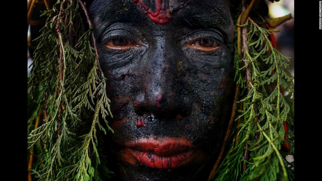 A man with a painted face takes part in the Gai Jatra (Cow Festival) in Kathmandu, Nepal, on Tuesday, August 8. Hindus celebrate Gai Jatra to ask for salvation and peace for their family members who have passed away. Cows are regarded as holy animals in Nepal, and according to belief they help departed souls reach heaven.