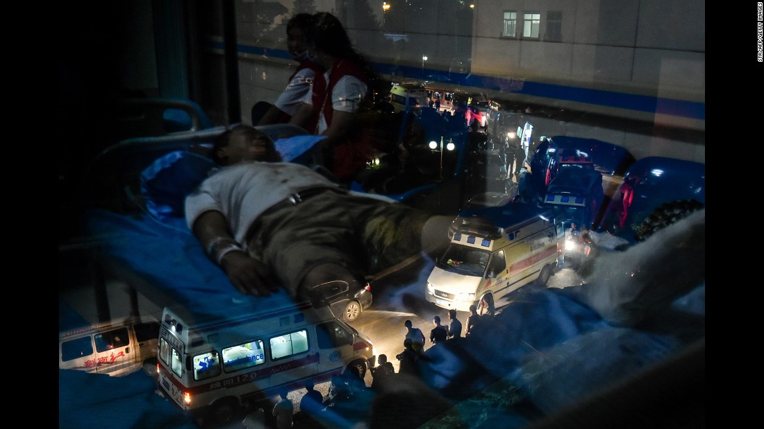"An earthquake survivor, lying on a hospital bed, is reflected in a window as ambulances line up outside the hospital in Jiuzhaigou, China, on Wednesday, August 9. <a href=""http://www.cnn.com/2017/08/08/asia/china-earthquake/index.html"" target=""_blank"">A powerful earthquake</a> struck the popular tourist area in southwest China."