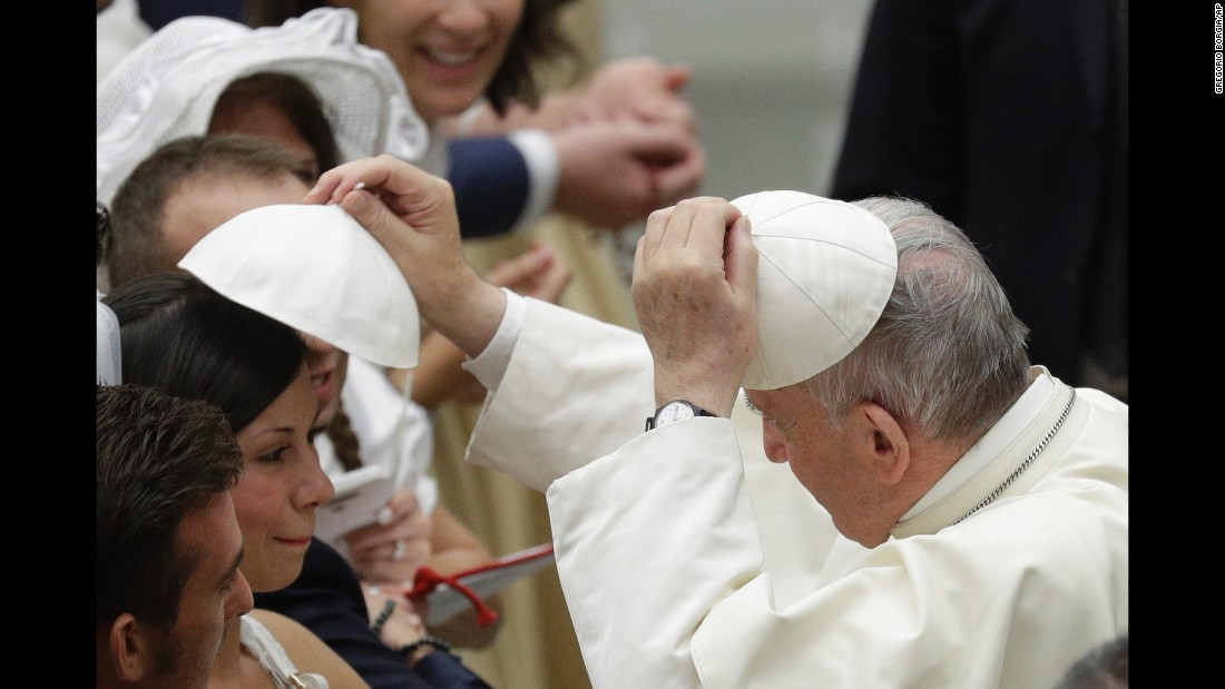 Pope Francis exchanges skullcaps with a woman during his weekly address at the Vatican on Wednesday, August 9.