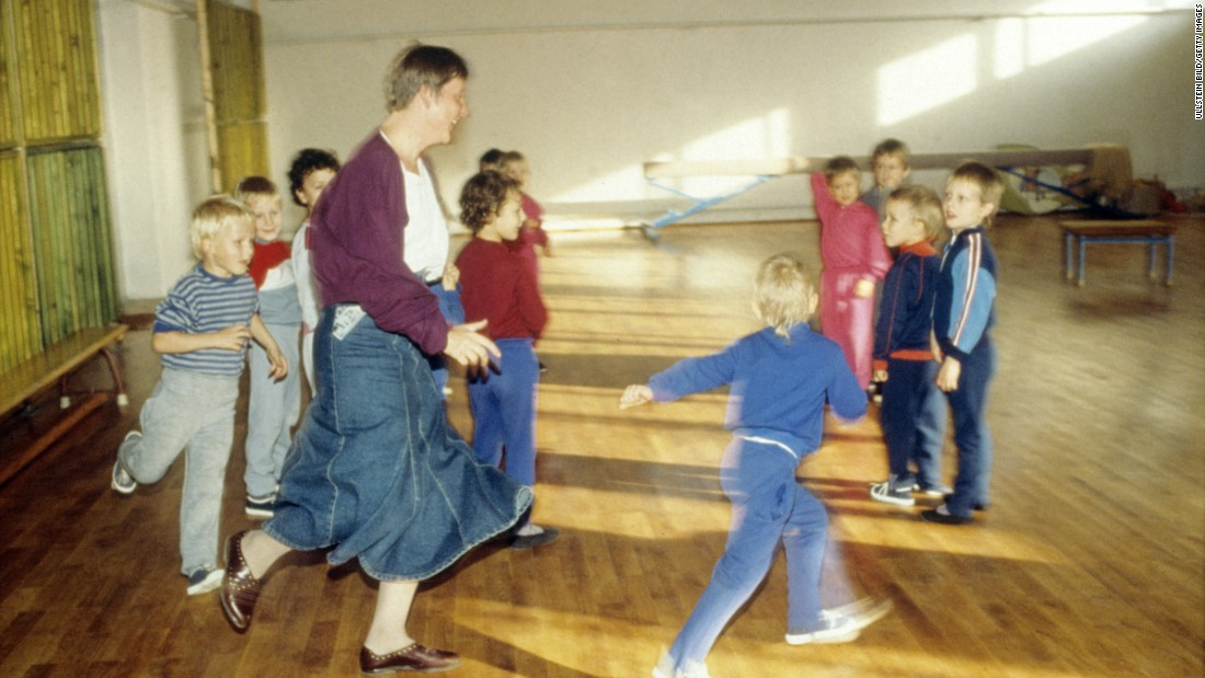"Merkel visits a children's home during her campaign to become a member of the Bundestag, Germany's parliament, in 1990. Before turning to politics, Merkel had trained as a physicist. She was also a spokeswoman for the ""Democratic Awakening,"" East Germany's opposition movement before reunification."