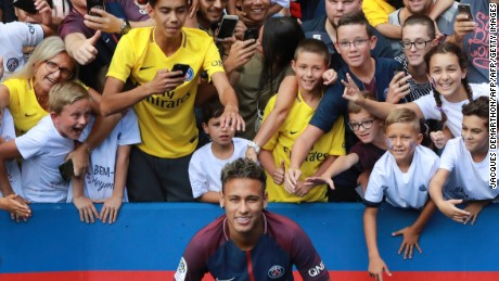 "Paris Saint-Germain's Brazilian forward Neymar poses for a photograph during his presentation to the fans at the Parc des Princes stadium in Paris on August 5, 2017. Brazilian superstar Neymar received a hero's welcome from Paris Saint-Germain fans at their Parc des Princes home on August 5, as he vowed to win ""lots of trophies"" following his world record transfer. The 25-year-old was presented to fans on the pitch ahead of their opening Ligue 1 match of the season at home to Amiens, telling fans: ""Thank you! I'm very happy, I'm delighted to be here for this new challenge.""   / AFP PHOTO / JACQUES DEMARTHON        (Photo credit should read JACQUES DEMARTHON/AFP/Getty Images)"
