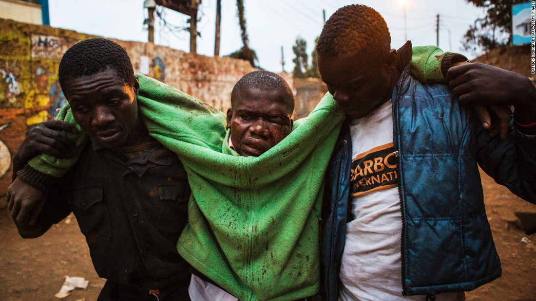 An injured man is carried in the Kibera slum of Nairobi.