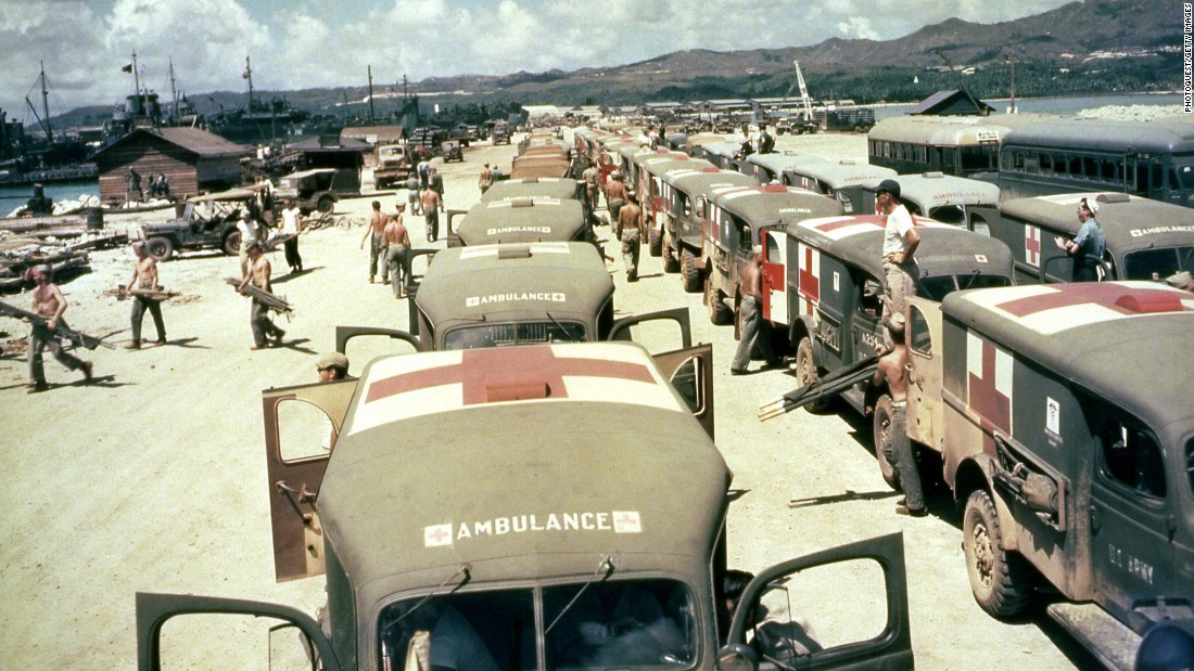 Military ambulances are lined up on shore at Guam, awaiting the arrival of the USS Solace with casualties from Okinawa, in June 1945.