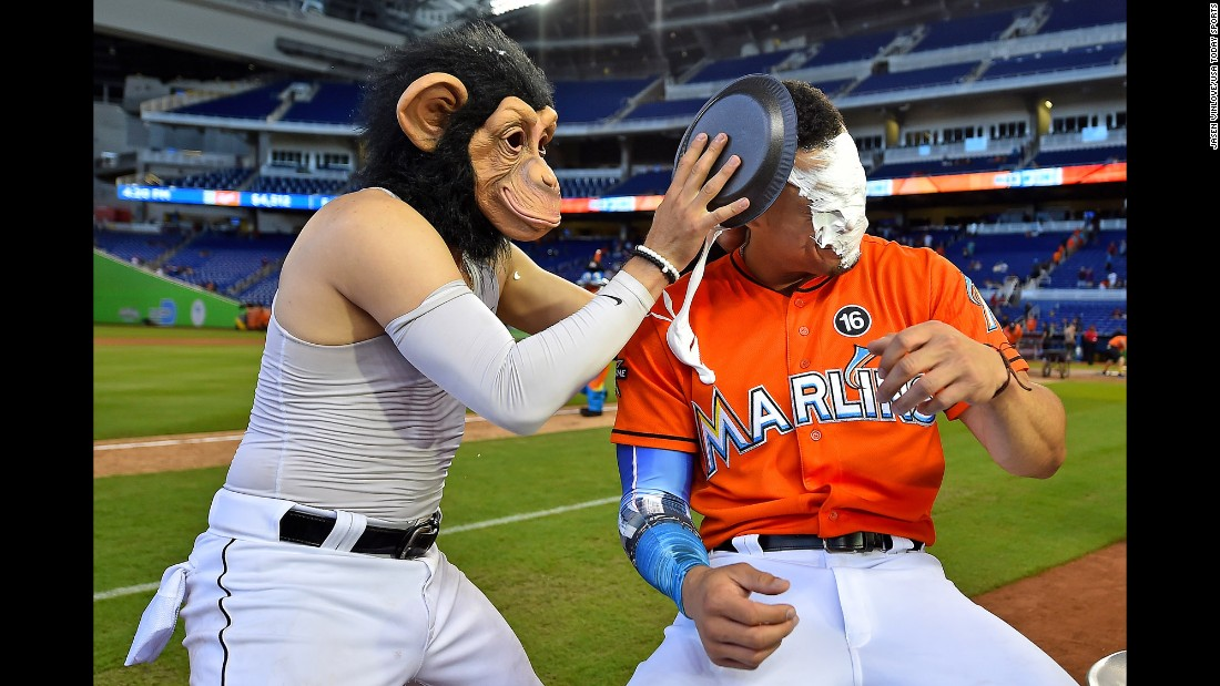 Miami Marlins shortstop Miguel Rojas, wearing a monkey mask, hits Giancarlo Stanton with a shaving-cream pie after their victory over Colorado on Sunday, August 13. Rojas has been doing this after big wins all season.