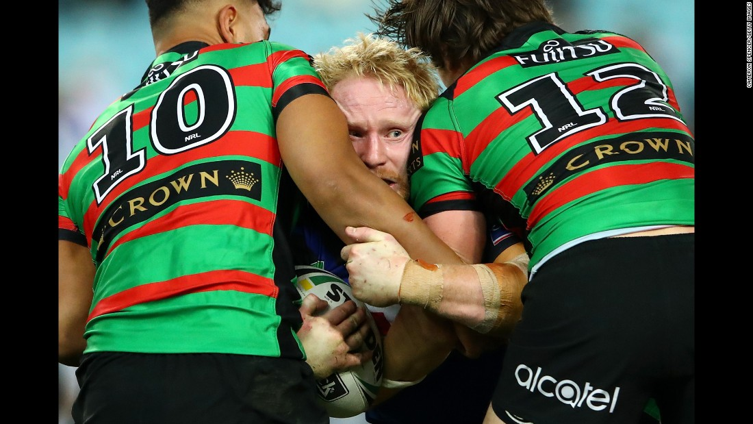 James Graham is tackled by two South Sydney Rabbitohs during a National Rugby League match in Sydney on Thursday, August 10.