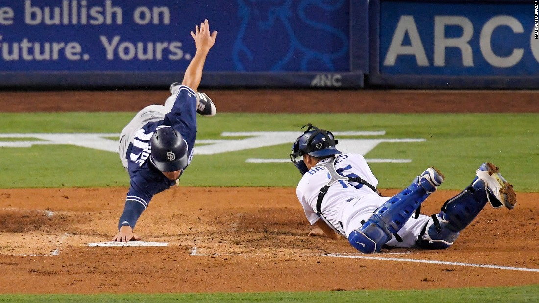 San Diego's Hunter Renfroe, left, reaches for the base after being tagged out by Los Angeles Dodgers catcher Austin Barnes on Friday, August 11.