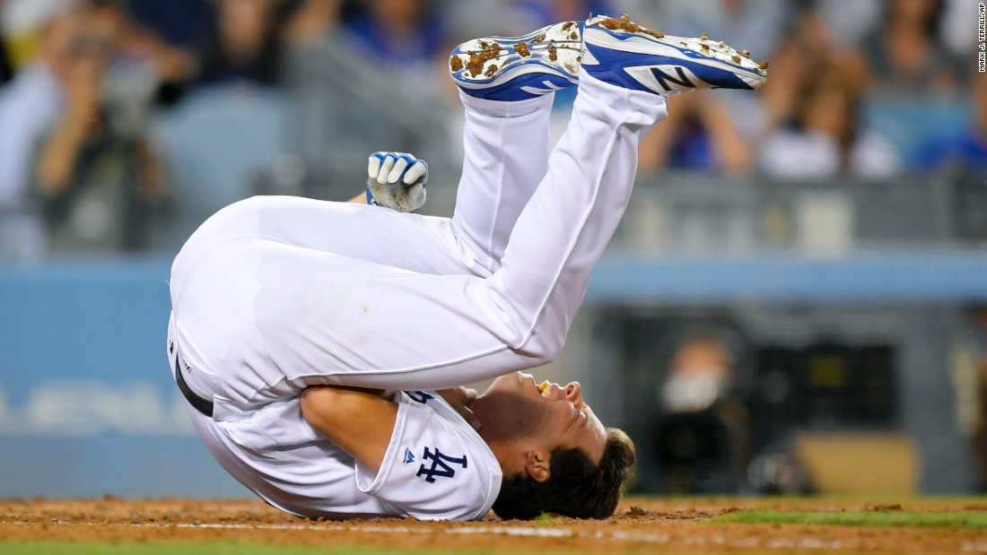 Rich Hill, a pitcher for the Los Angeles Dodgers, writhes on the ground after getting hit in the throat with a fastball on Friday, August 11. He stayed in the game.